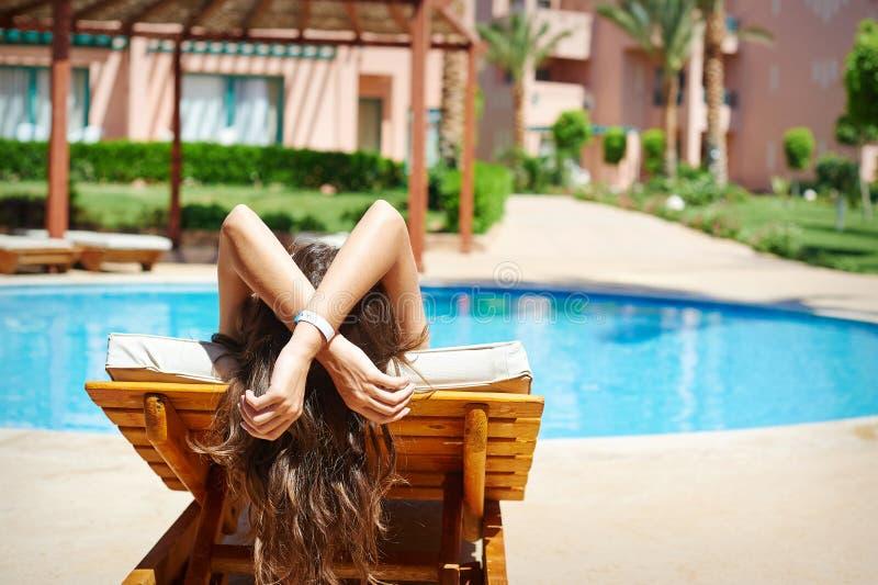 De jonge mooie glimlachende vrouwenzwemmer ontspant op een lanterfanter door de pool stock foto's