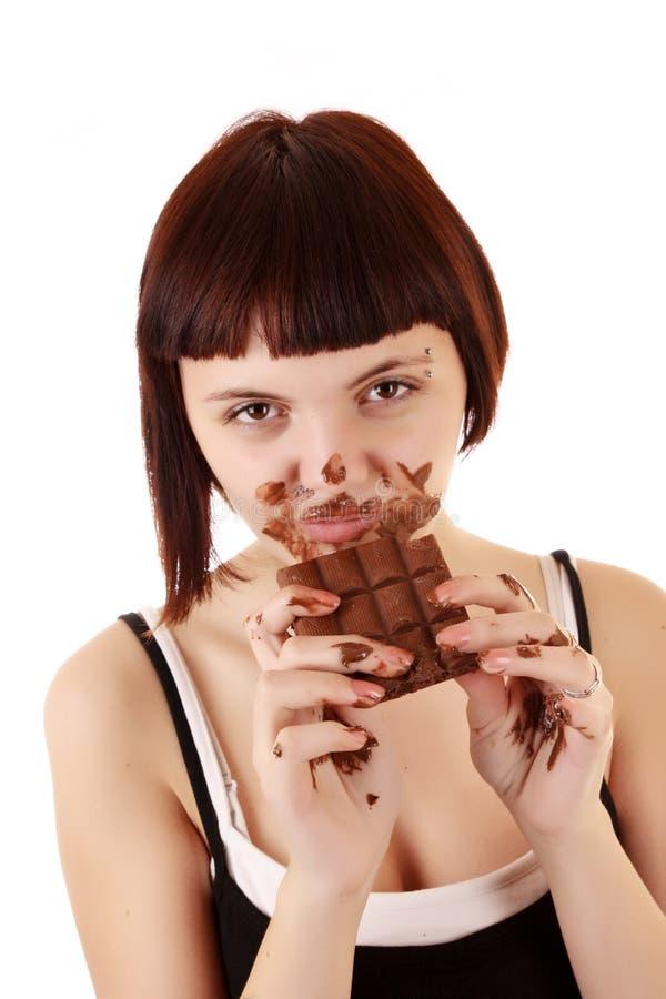 De jonge mooie gourmand eet geïsoleerden chocolade royalty-vrije stock foto