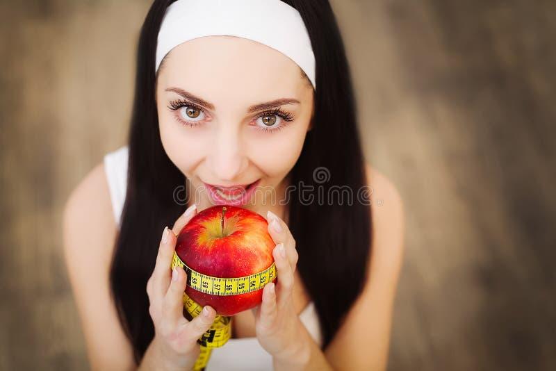De jonge mooie het glimlachen rode appel van de vrouwen bevindende holding Concept FO royalty-vrije stock afbeelding
