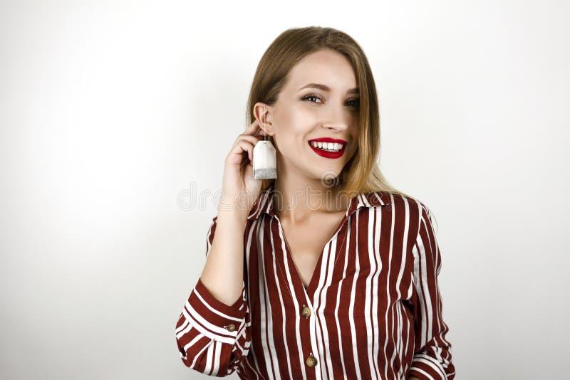 De jonge mooie de holdingsthee van de blonde grappige vrouw als oorringszak isoleerde witte achtergrond stock afbeelding