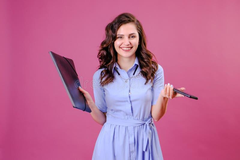 De jonge mooie Kaukasische vrouw met een glimlach kijkt aan camera houdend haar van het celtelefoon en document omslag op een roz royalty-vrije stock foto's