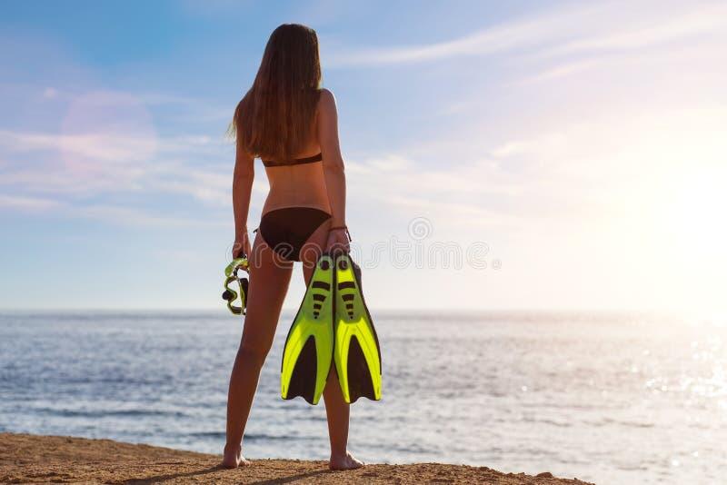 De jonge mooie meisje status met snorkelt en vinnen dichtbij het overzees stock foto's