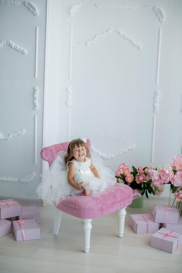 De jonge mooie meisjesballerina in een witte roze kleding bevindt zich in een witte ruimte dichtbij een witte lijst houdt een boe stock afbeeldingen