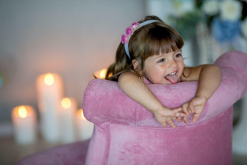 De jonge mooie meisjesballerina in een witte roze kleding bevindt zich in een witte ruimte dichtbij een witte lijst houdt een boe royalty-vrije stock afbeeldingen