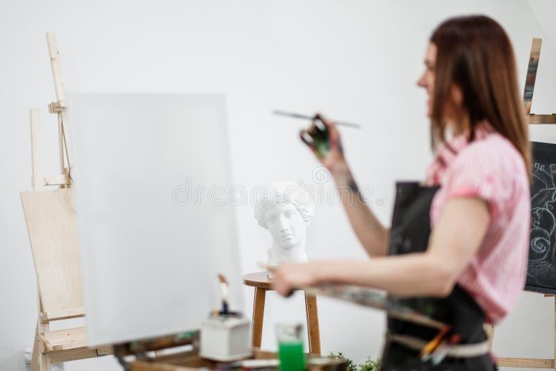 De jonge mooie meisjesschilder in een witte studio trekt op een schildersezel op canvas royalty-vrije stock fotografie