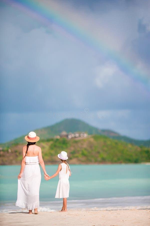 De jonge mooie moeder en haar aanbiddelijke kleine dochter hebben pret bij tropisch strand royalty-vrije stock foto's