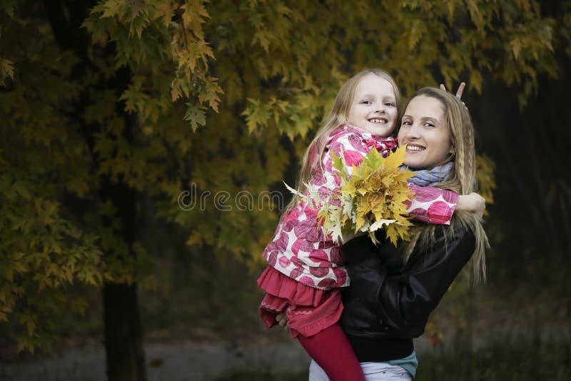 De jonge mooie moeder houdt haar meisje die in de herfstpark de camera bekijken royalty-vrije stock foto's