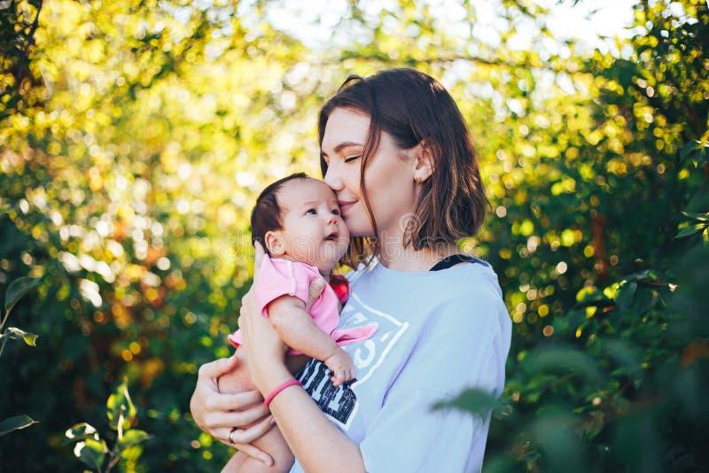 de jonge mooie moeder met donker haar houdt haar pasgeboren babymeisje royalty-vrije stock foto's