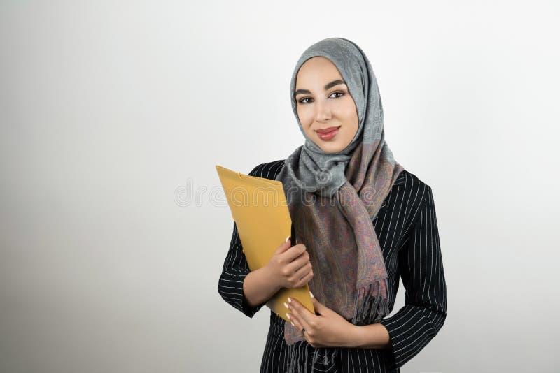 De jonge mooie Moslim bedrijfsvrouw die de omslag van de tulband hijab headscarf holding met documenten dragen isoleerde wit royalty-vrije stock afbeeldingen