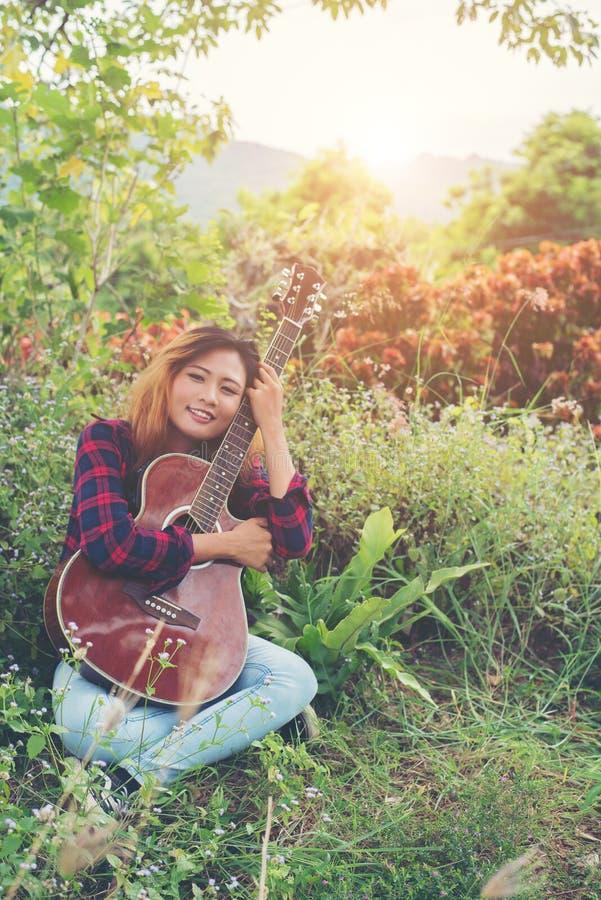 De jonge mooie omhelzing van de hipstervrouw met haar gitaarzitting op gra stock fotografie