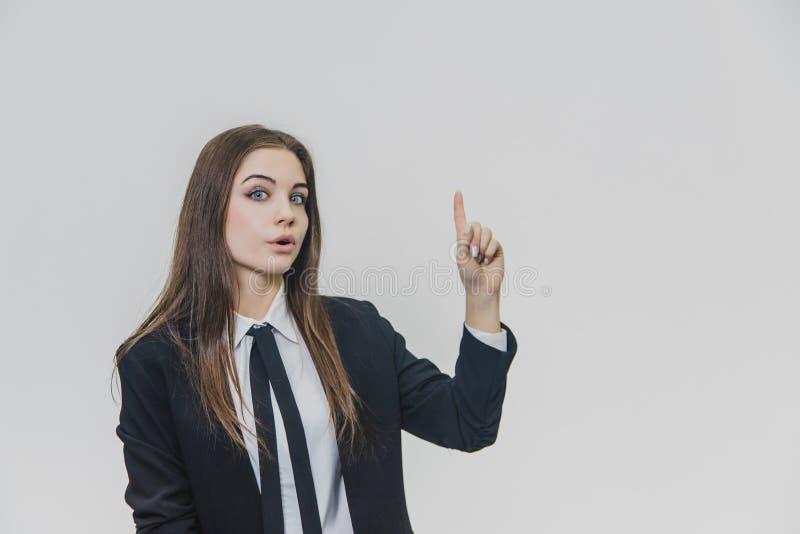 De jonge mooie onderneemster benadrukt haar vinger met een vermaak, een verbazing en een verblindende gelaatsuitdrukking royalty-vrije stock afbeelding