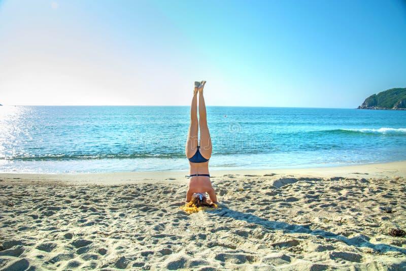 De jonge, mooie, roodharige yoga van meisjespraktijken op het strand stock foto