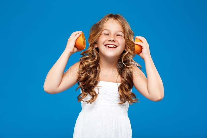 De jonge mooie sinaasappelen van de meisjesholding, die over blauwe achtergrond glimlachen stock afbeelding