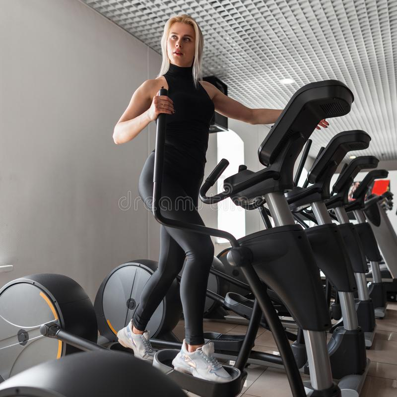 De jonge mooie sportieve vrouw in zwarte modieuze kleren in tennisschoenen doet cardio opleiding op een simulator in de gymnastie royalty-vrije stock foto