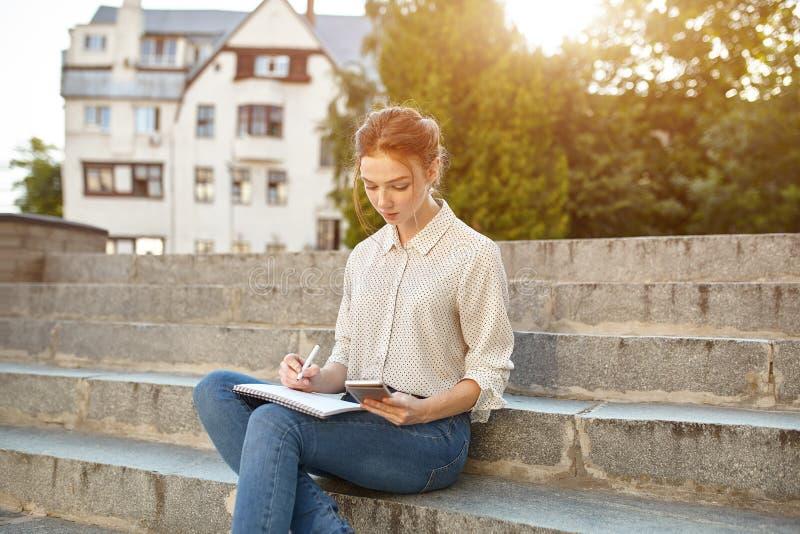De jonge mooie student schrijft een poging in haar notitieboekjezitting op het openlucht Roodharige meisje van stappentreden met  royalty-vrije stock afbeeldingen