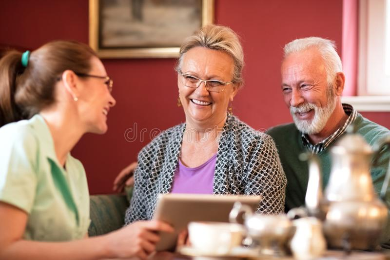 De jonge mooie verpleegster neemt zorg over oude mensen stock afbeeldingen