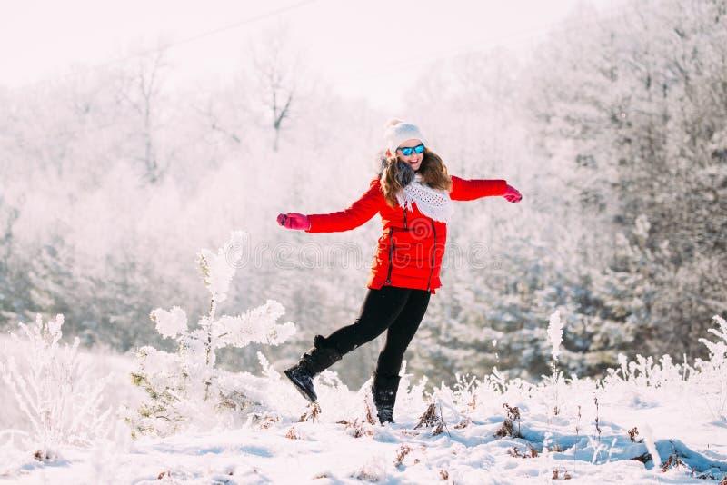 De jonge Mooie vrij Kaukasische Meisjesvrouw in Blauwe Zonnebril kleedde zich in Rood en Jasje en Witte Hoed die glimlachen sprin stock foto