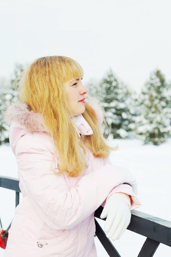 De jonge mooie vrouw ademt verse lucht en heeft een rust openlucht in de winter royalty-vrije stock afbeeldingen