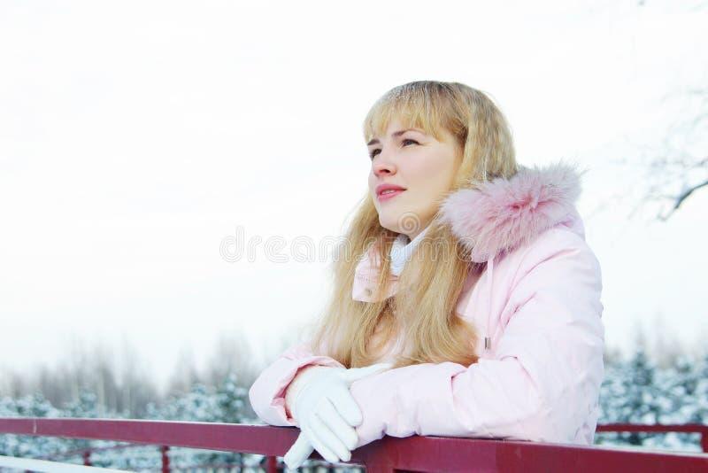 De jonge mooie vrouw ademt verse lucht en heeft een rust in de winter stock fotografie