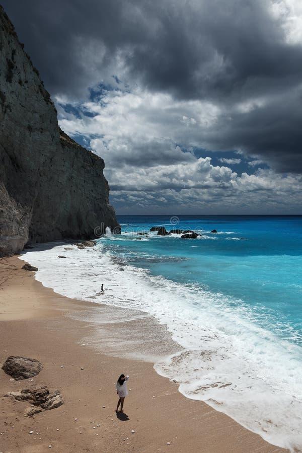 De jonge mooie vrouw bekijkt het overzees op het Porto Katsiki strand, het eiland van Lefkada, Griekenland stock afbeelding