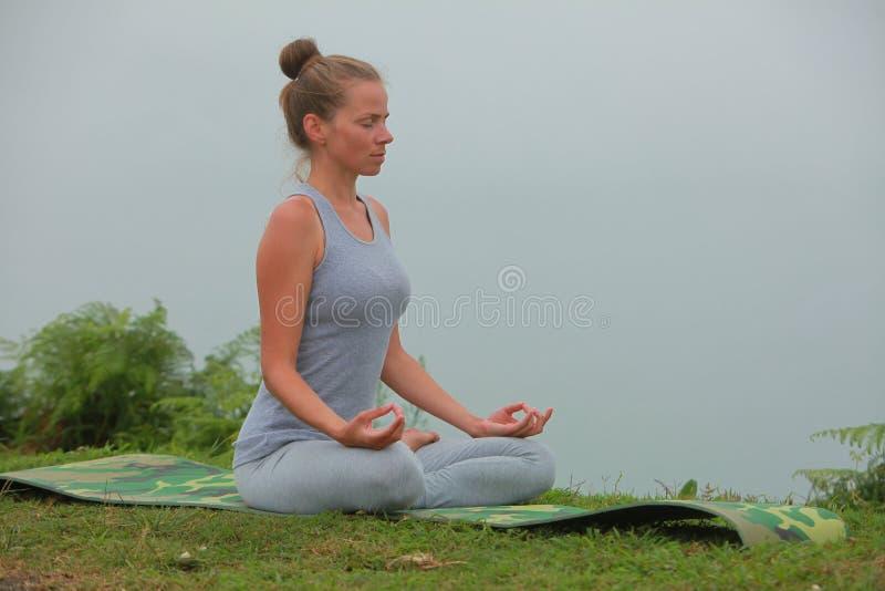 De jonge mooie vrouw is bezig geweest met hathayoga in de ochtend nevelige bergen stock afbeeldingen