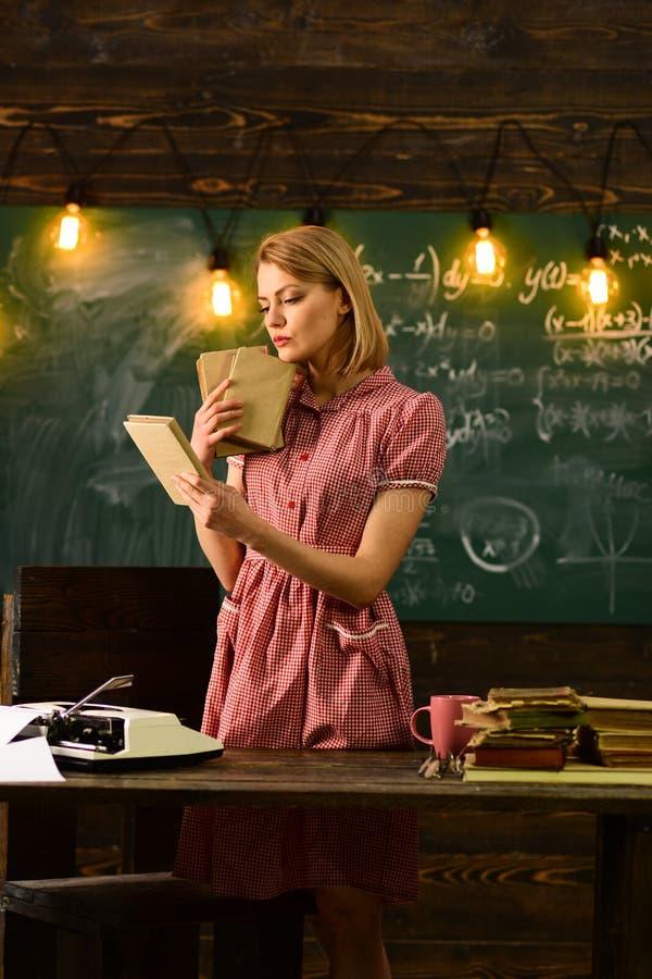 De jonge mooie vrouw bij schoolbord dichtbij koffiekop en de lezing een boek van rust geniet van graven in lezing stock afbeelding