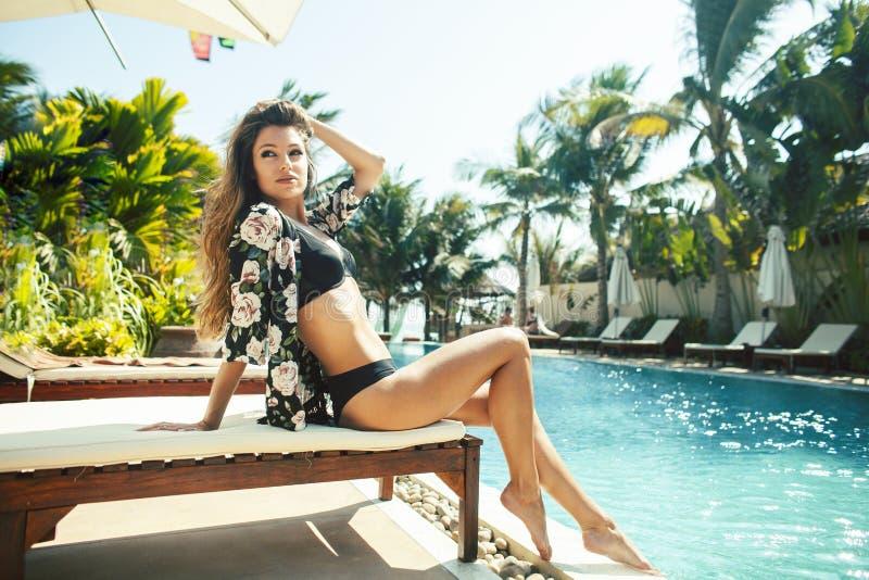 De jonge mooie vrouw bij zwembad het ontspannen als voorzitter, manier bekijkt in lingerie hotel, het concept van levensstijlmens royalty-vrije stock afbeeldingen
