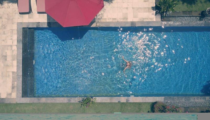 De jonge mooie vrouw in de vlakke pool, legt, dron mening, retro effect stock foto's