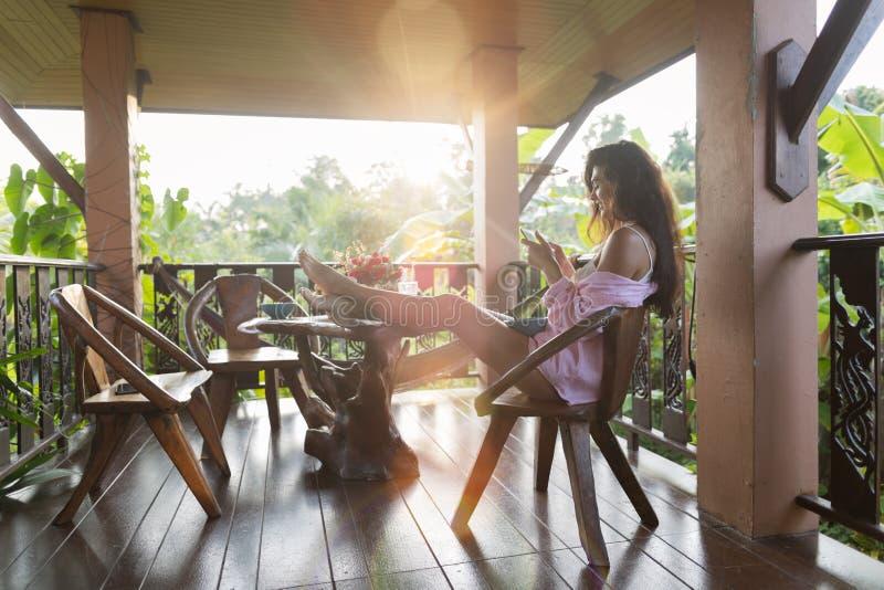 De jonge Mooie Vrouw die Cel Slimme Telefoon Sit On Terrace With Tropical Forest Landscape And Morning Sun met behulp van glanst royalty-vrije stock afbeelding