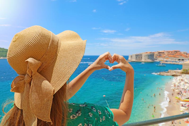 De jonge mooie vrouw die in Dubrovnik handen maken vormde hart op de warme zonnige dag van de de lentezomer Meisje met hoed in op stock foto