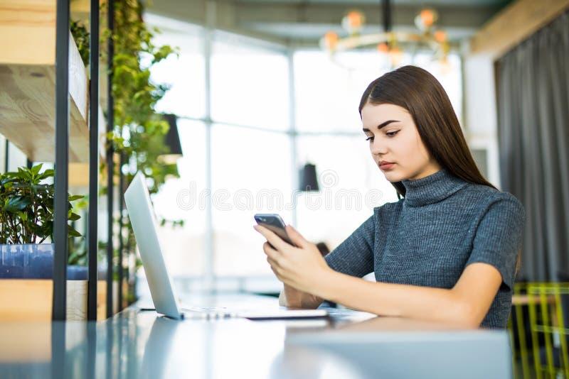 De jonge mooie vrouw die glazen dragen, die in het bureau werken, gebruikt laptop en een mobiele telefoon stock afbeeldingen