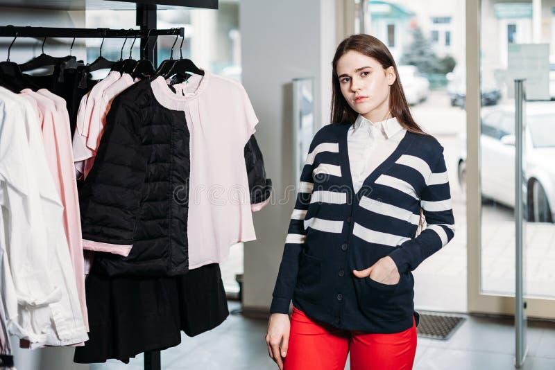 De jonge mooie vrouw die, proberend en koopt kleding bij winkelkleding kiezen stock foto's