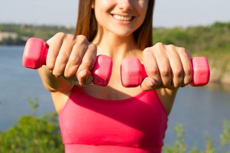 De jonge mooie vrouw die sportoefeningen met domoren doen overtreft stock afbeelding