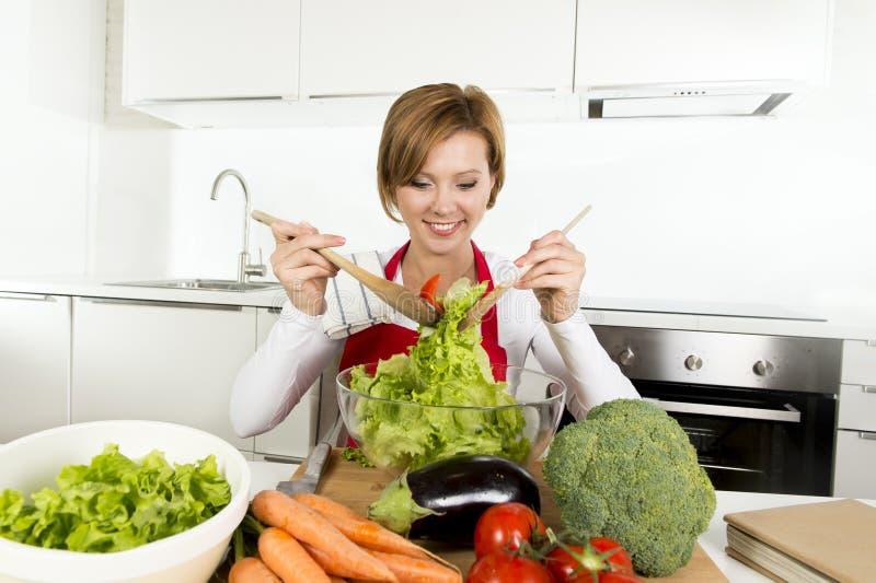 De jonge mooie vrouw die van de huiskok bij moderne keuken het plantaardige saladekom gelukkig glimlachen voorbereiden royalty-vrije stock fotografie