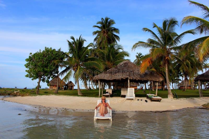 De jonge mooie vrouw die van haar tijd genieten en dicht bij het overzees in het privé strand van Yandup-Eiland rusten brengt in  royalty-vrije stock fotografie