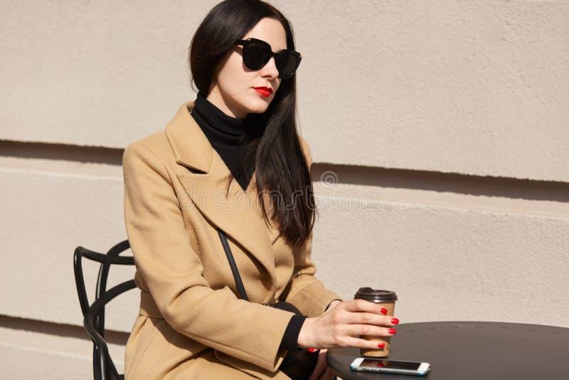 De jonge mooie vrouw drinkt hete drank terwijl het wachten van haar partner bij openluchtkoffie in middag Donkerbruin meisje met  royalty-vrije stock fotografie