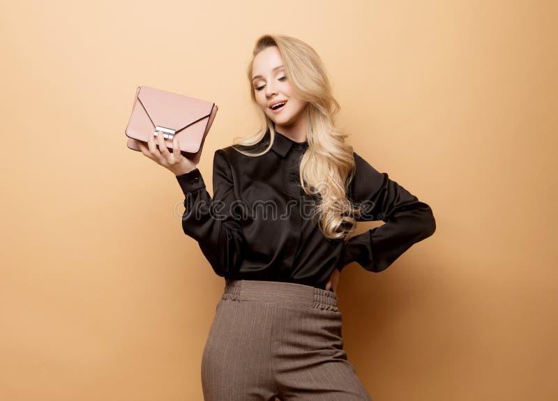 De jonge mooie vrouw in een bruine blouse en broek houdt een handtas en het stellen op een beige achtergrond royalty-vrije stock foto