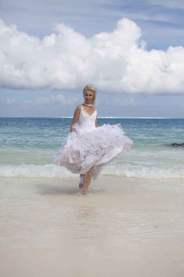 De jonge mooie vrouw in een kleding van de bruidlooppas op golven van het overzees stock afbeeldingen