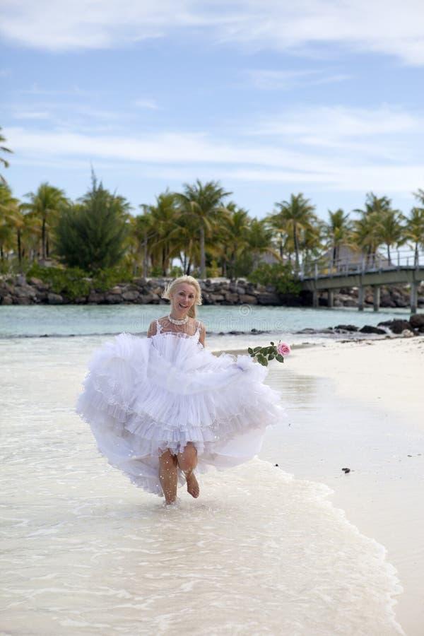 De jonge mooie vrouw in een kleding van de bruidlooppas op golven van het overzees royalty-vrije stock foto