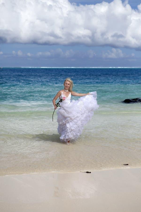 De jonge mooie vrouw in een kleding van de bruidlooppas op golven van het overzees royalty-vrije stock afbeelding