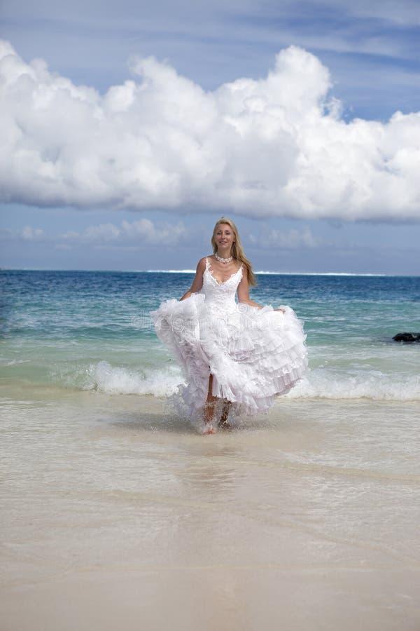 De jonge mooie vrouw in een kleding van de bruidlooppas op golven van het overzees royalty-vrije stock fotografie