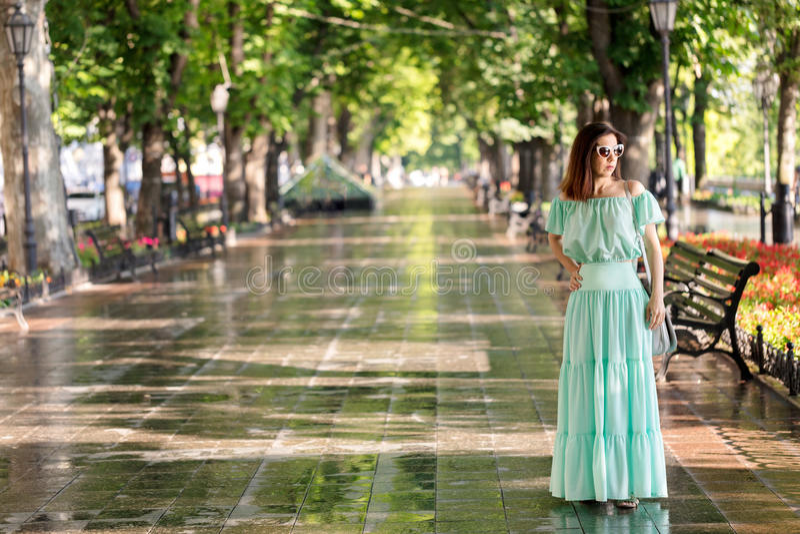 De jonge mooie vrouw in een lichtgroene pastelkleur lange kleding is gang royalty-vrije stock fotografie