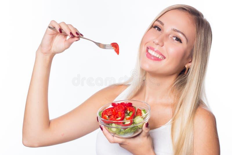 De jonge mooie vrouw eet plantaardige salade Het gezonde Eten Om te zijn in vorm stock foto's