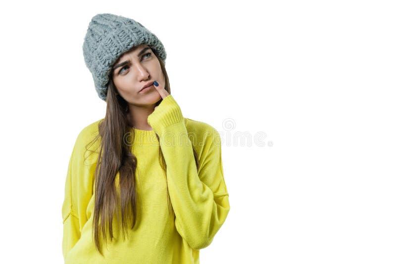 De jonge mooie vrouw in gele sweater en grijze grote lijn breide beanie hoed, nadenkende holding een vinger dichtbij haar lippen, royalty-vrije stock foto