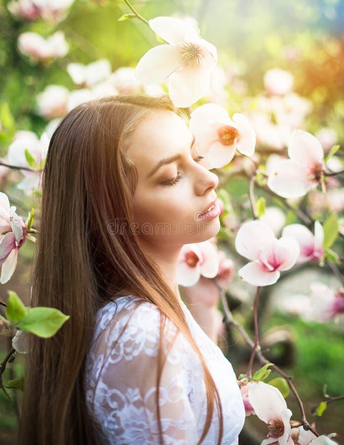 De jonge mooie vrouw geniet van in mooi park dichtbij bloemen royalty-vrije stock afbeeldingen
