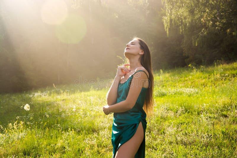 De jonge mooie vrouw geniet van zonlicht, die haar handen omhoog op a opheffen stock afbeeldingen