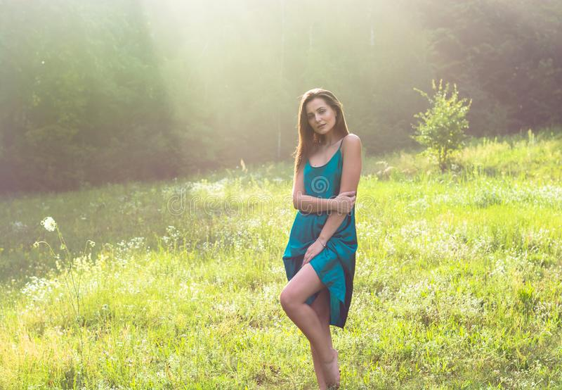 De jonge mooie vrouw geniet van zonlicht op een bloemweide bij zonnen stock afbeelding