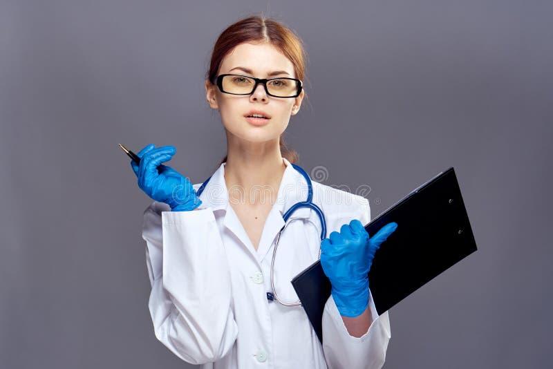 De jonge mooie vrouw in glazen op een grijze achtergrond houdt een omslag met documenten en pen, arts, geneeskunde royalty-vrije stock foto