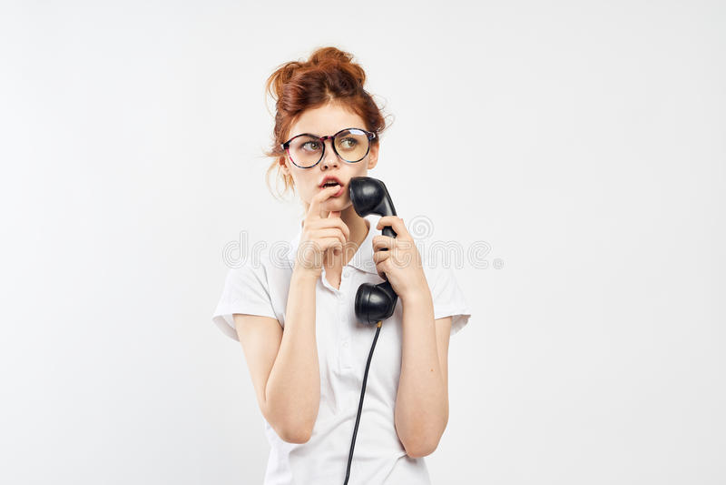 De jonge mooie vrouw in glazen op een wit geïsoleerde achtergrond houdt een oude telefoon, mededeling stock foto