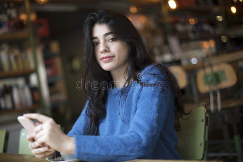 De jonge mooie vrouw het drinken koffie en gebruikt haar smartphonezitting binnen in stedelijke koffie De levensstijl van de koff stock afbeeldingen